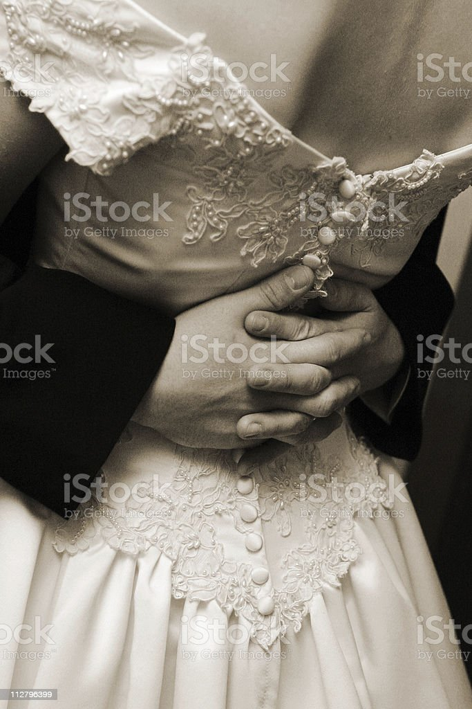 Close up Grooms hand on Brides back first dance sepia royalty-free stock photo