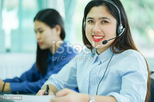 1142008983 istock photo close up group employee call center woman agent wear headset device smiling with colleague on desktop pc table  at operation room , telemarketing and help desk concept 1135729683