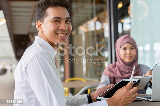 481711196istockphoto close up group of asian muslim young student man and woman studying together at outside library for research data and doing homework or project on laptop and tablet , millennial lifestyle education concept 1163630466
