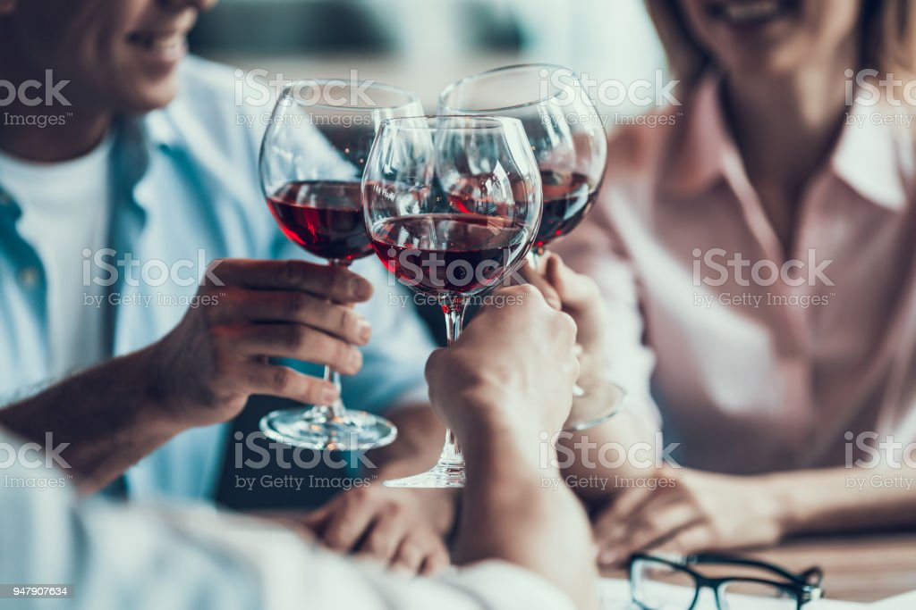 Close up. Group of business people cheering with wine glass at cafe. stock photo