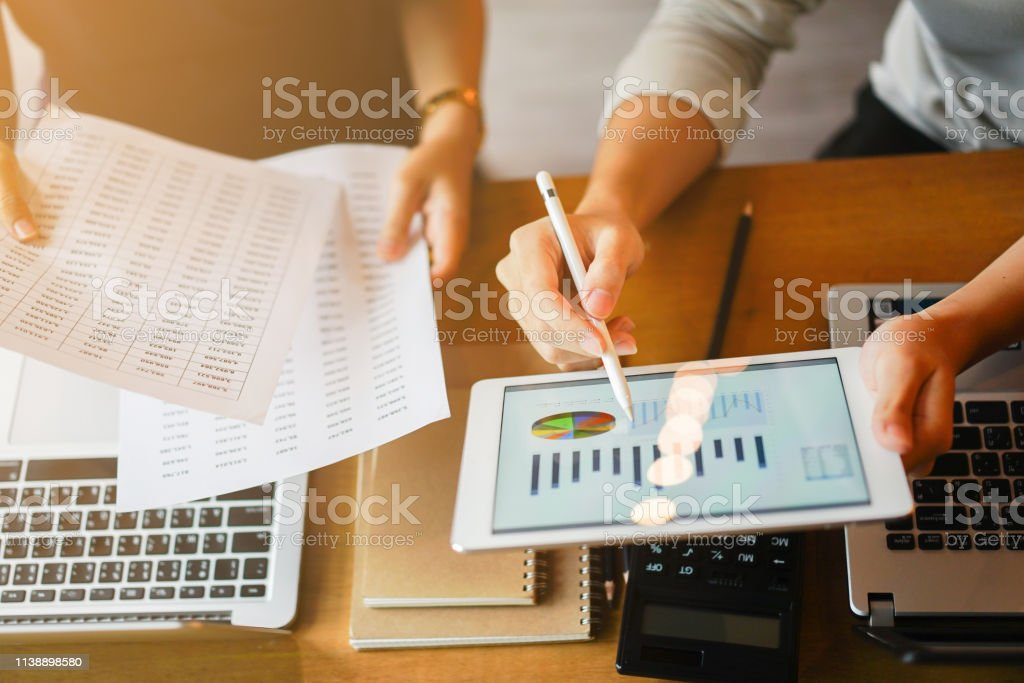 close up group of businessman use stylus pen for explaining dashboard about company's profit monthly on tablet and businesswoman holding report paper for collaborate  work at meeting event , business finance concept close up group of businessman use stylus pen for explaining dashboard about company's profit monthly on tablet and businesswoman holding report paper for collaborate  work at meeting event , business finance concept Accountancy Stock Photo