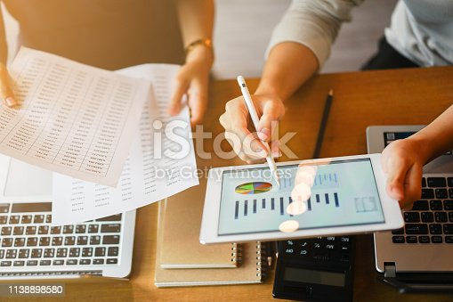 close up group of businessman use stylus pen for explaining dashboard about company's profit monthly on tablet and businesswoman holding report paper for collaborate  work at meeting event , business finance concept