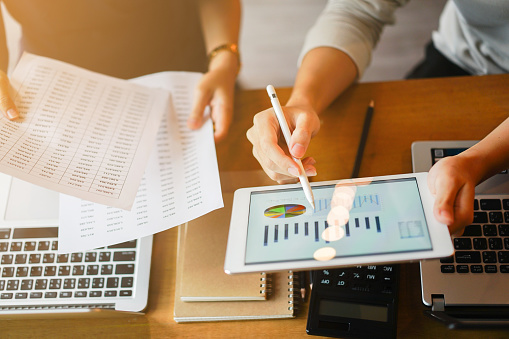 Close Up Group Of Businessman Use Stylus Pen For Explaining Dashboard About Companys Profit Monthly On Tablet And Businesswoman Holding Report Paper For Collaborate Work At Meeting Event Business Finance Concept Stock Photo - Download Image Now