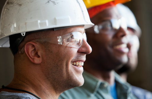 Close up of group of multi-ethnic construction workers wearing hard hats and safety glasses.  Focus on man in foreground (30s).
