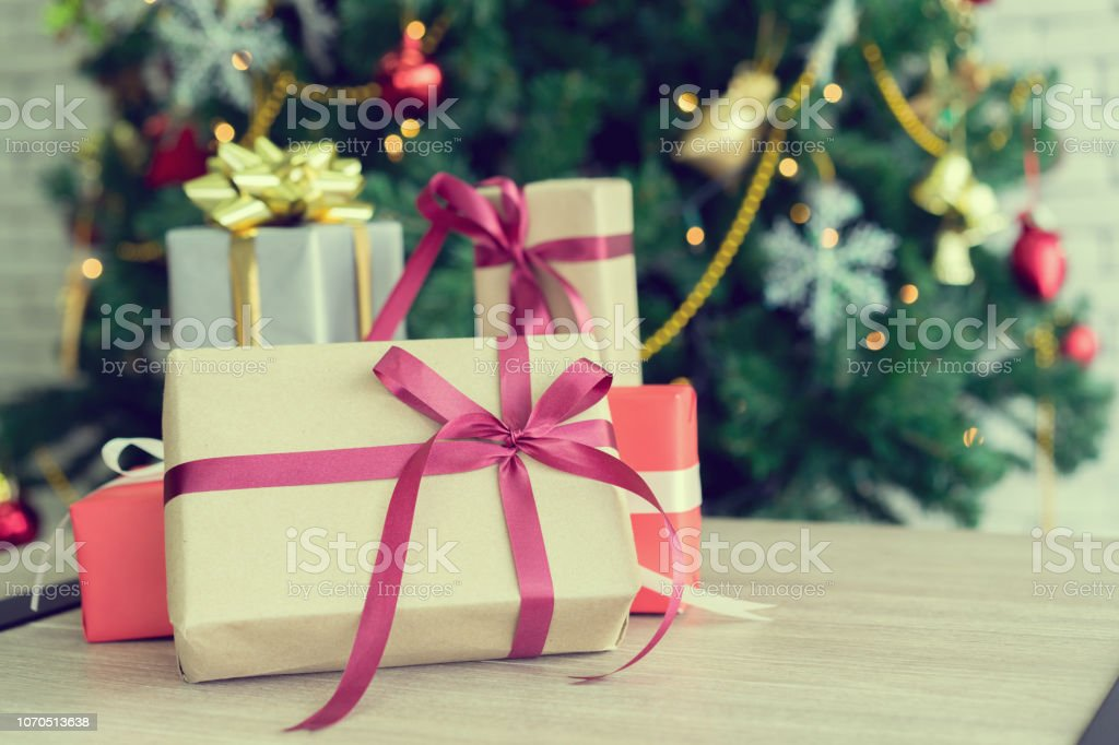 close up group of gift boxes on wood tabletop with christmas pin tree decoration for xmas and happy new year festival celebration concept stock photo