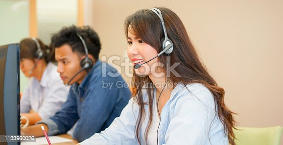 1142008983 istock photo close up group of multi ethnic young employee call center agent wear headset device smiling with service-mind on desktop pc table  at operation room , telemarketing and help desk concept 1133960026