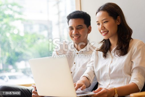 close up group of multi-ethnicity couple sitting on couch sofa and playing on laptop together at the living room in leisure weekend time for family lifestyle and lover life concept