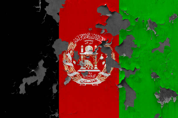 Close up grungy, damaged and weathered Afghanistan flag on wall peeling off paint to see inside surface. stock photo