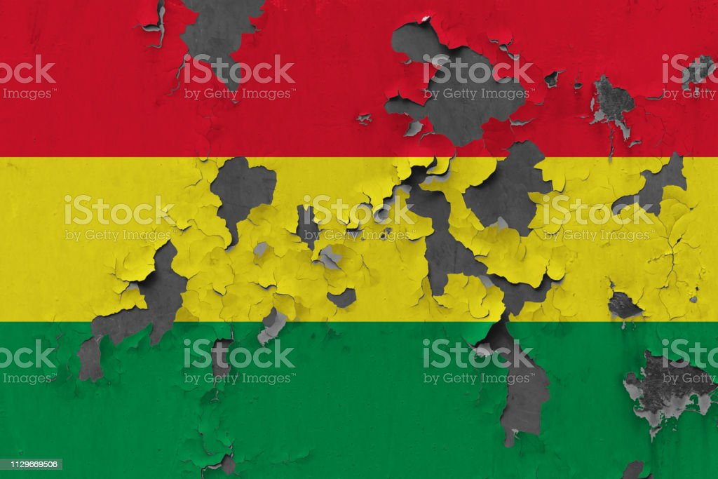 Close up grungy, damaged and weathered Bolivia flag on wall peeling off paint to see inside surface. stock photo
