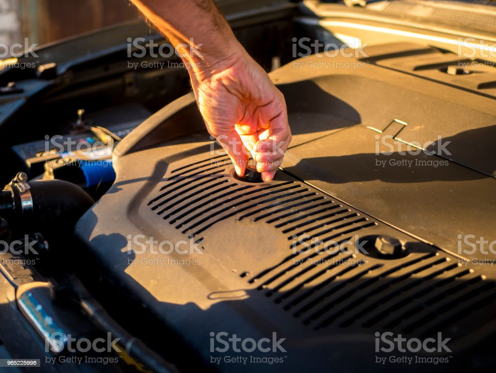close up hand adjusting car mechanic opening hood during sunset zbiór zdjęć royalty-free