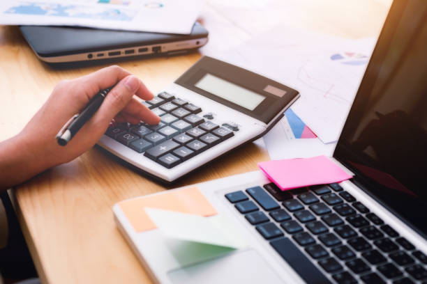 Close up hand Business woman using a calculator to calculate analyzing investment. Accounting and technology in office. business workplace strategy Concept. stock photo