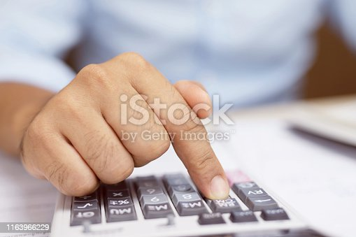 879813798istockphoto close up hand businessman using electronic calculator calculating data number on office desk table wooden. copy space 1163966229