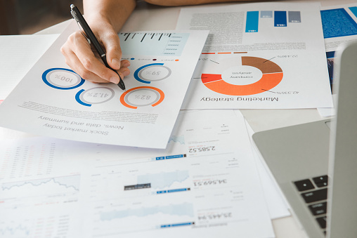 1044507110 istock photo Close up hand Businesswoman holding pen and pointing at financial paperwork and planning investment for business and stocks. 1254551336