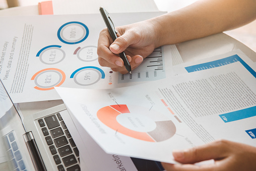 1044507110 istock photo Close up hand Businesswoman holding pen and pointing at financial paperwork and planning investment for business and stocks. 1254551422