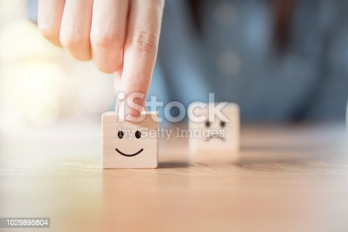 Close up costomer hand choose smiley face and blurred sad face icon on wood cube, Service rating, satisfaction concept.