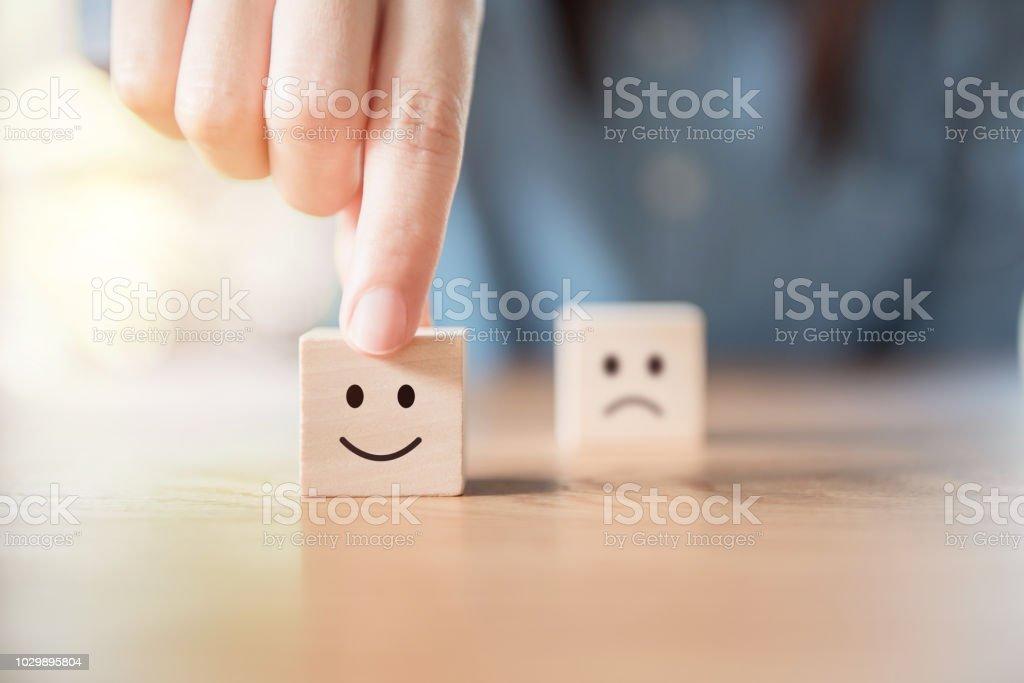 Nahaufnahme der Hand wählen Sie Smiley-Gesicht und unscharfen Bedrücktes Gesichtssymbol auf Holz Würfel – Foto