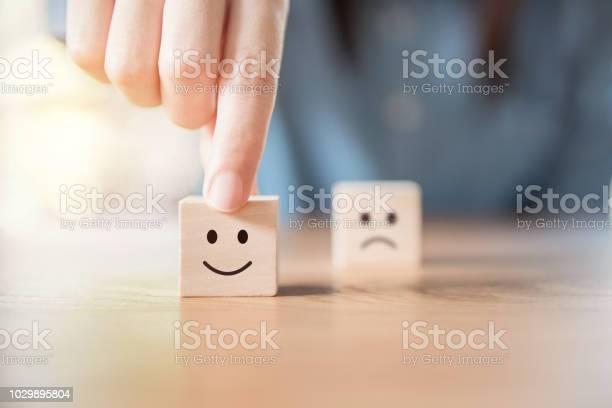 Close Up Hand Choose Smiley Face And Blurred Sad Face Icon On Wood Cube — стоковые фотографии и другие картинки Азиатского и индийского происхождения