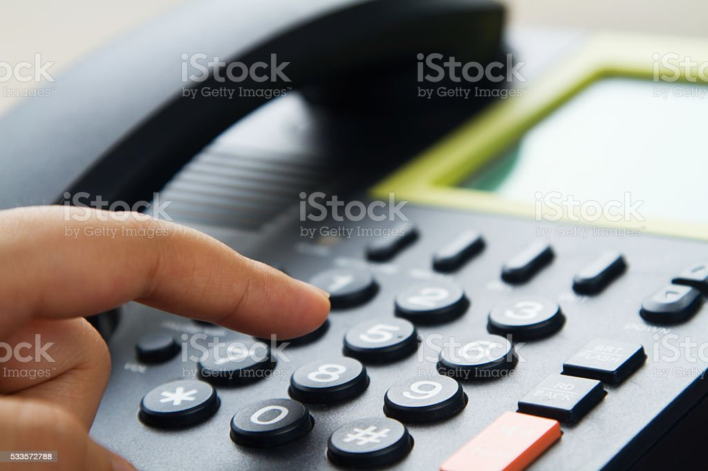 Close up hand dialing telephone stock photo