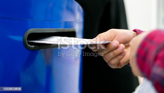 istock close up hand drop letter and documents in the blue postbox in post office mail f 1053603806