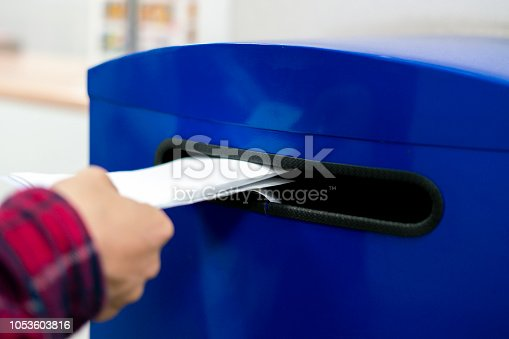 istock close up hand drop letter and documents in the blue postbox in post office mail f 1053603816