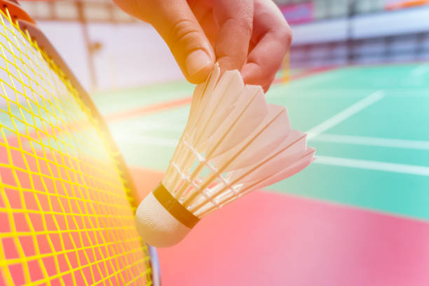 close up hand hold serve badminton shuttlecock with blur badminton court background close up hand hold serve badminton shuttlecock with blur badminton court background badminton stock pictures, royalty-free photos & images