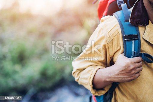 istock close up hand holding backpack man hiking traveling on forest in travel Lifestyle wanderlust adventure with enjoying on nature. Tourist traveler on background valley landscape view. focus to hand. 1186082087