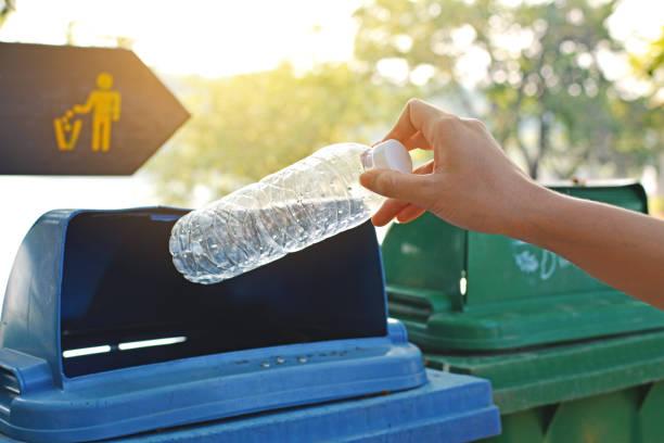 fermer la main retenant la bouteille vide dans la poubelle - recyclage main photos et images de collection