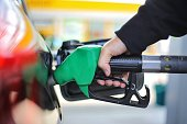 istock Close up hand holding green gasoline fuel nozzle and being fill gas tank of black car in gas station Concept of Global Fossil Fuel Consumption.  Replace by alternative energy in near the near future 1152189445