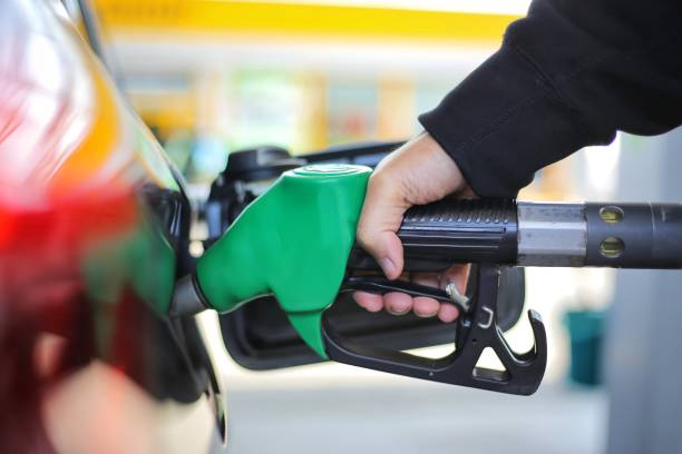 close up hand holding green gasoline fuel nozzle and being fill gas tank of black car in gas station concept of global fossil fuel consumption.  replace by alternative energy in near the near future - benzina foto e immagini stock