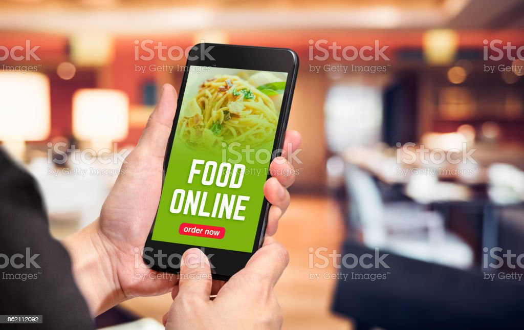 Close up hand holding mobile phone with order food online word on screen with blur restaurant bokeh light background,online food marketing concept. stock photo