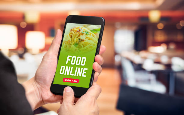 close up hand holding mobile phone with order food online word on screen with blur restaurant bokeh light background,online food marketing concept. - ordine foto e immagini stock