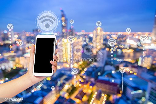 istock Close up hand holding phone with WiFi icon over night city, internet and connection concept 1024708996