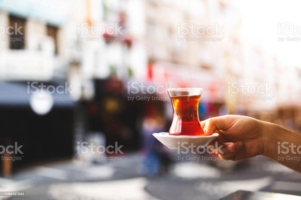 Close up hand holding Turkish tea over