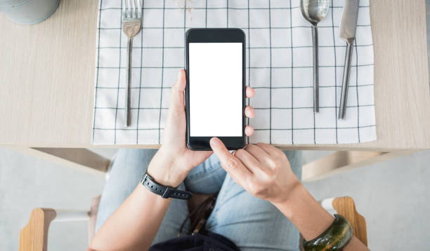 close up hand holding white blank screen over restaurant table stock photo