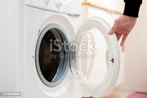 close up hand launch set and start washing machine laundry at home bathroom