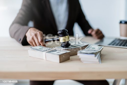 1050485096 istock photo close up hand lawyer with wooden auction judge hammer with money blur background 1057984938