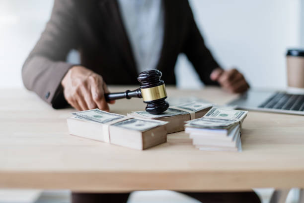 close up hand lawyer with wooden auction judge hammer with money blur background close up hand lawyer with wooden auction judge hammer with money blur background punishment stock pictures, royalty-free photos & images