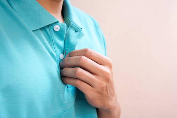 Close-up homens de mão, ajuste o botão de t-shirt verde esmeralda - foto de acervo