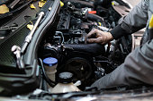 istock Close up hand of auto mechanic doing car service and maintenance. Services car engine machine. 1189380098