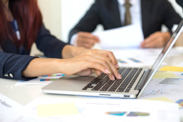 close up hand of business woman employees secretary using laptop  minutes  of executive meeting - business concept stock photo