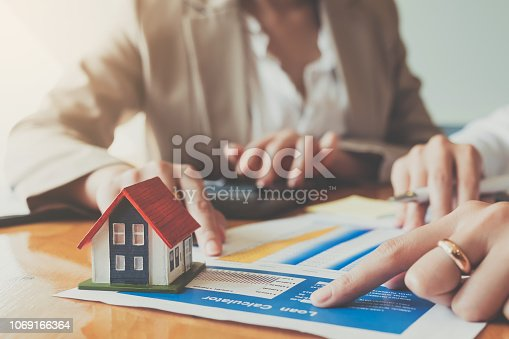 Close up hand of businesswoman signing contract Insurance protecting house.