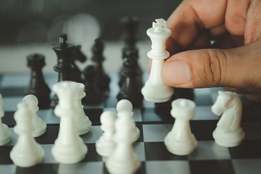 Close up hand of man hold the chess piece by hand to play chess game board for competition, Chess game are training strategy and thinking