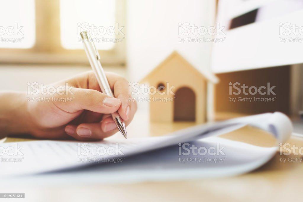 Cerrar una mano de hombre firme firma préstamo de propiedad de la vivienda. Hipotecario e inmobiliario propiedad de inversión - foto de stock