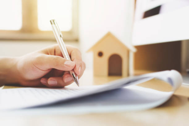Close up hand of man signing signature loan document to home ownership. Mortgage and real estate property investment - foto stock