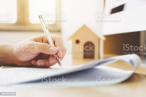 Close up hand of man signing signature loan document to home ownership. Mortgage and real estate property investment