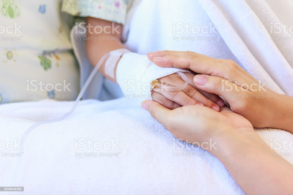 Close up hand of parent holding hand child in hospital. stock photo
