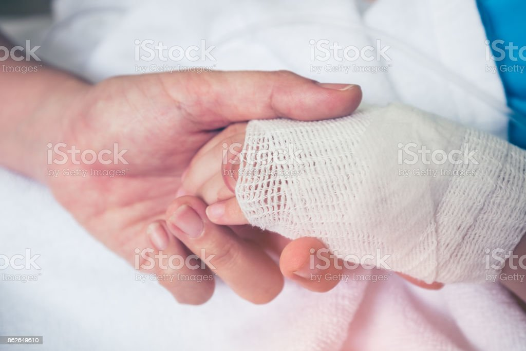 Close up hand of parent holding hand of child in hospital. Retro style. stock photo
