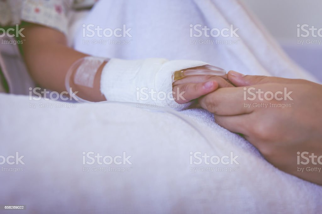 Close up hand of parent holding hand of child. stock photo