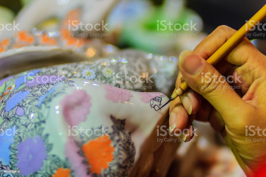 Close up hand of Thai woman artist during painting the masterpiece of Benjarong patterns, the famous thai 5- colored porcelain ceramic wares. stock photo