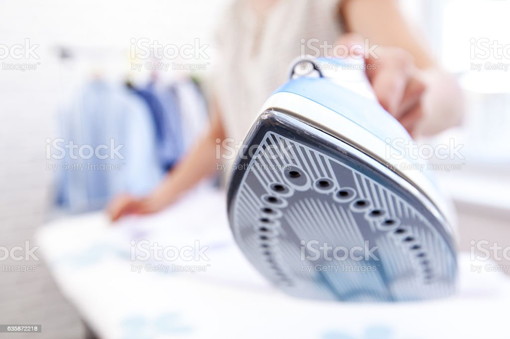 close up hand of woman ironing clothes on the table stock photo